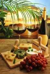 Käseplatte und Rotwein bei Sonnenuntergang