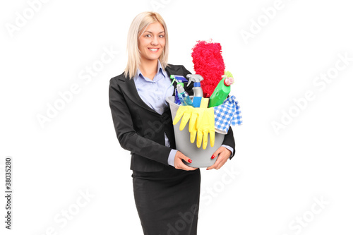A smiling female holding a bucket full with cleaning supplies