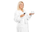 A young woman in bathrobe holding a coffee cup and mobile phone