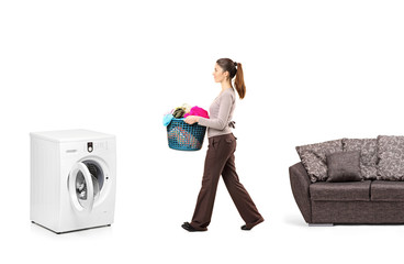 Housewife holding a laundry basket and going towards a washing m