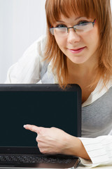 girl with glasses shows a finger on a laptop