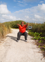 Handsome personal trainer exercising in a South Beach park