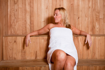 Mature woman enjoying a hot sauna
