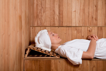 Young woman relaxing in a hot sauna