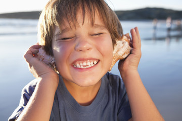 Close up of enthusiastic boy holding seashells to ears on beach