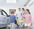 Family with beach items in driveway