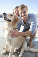 Smiling couple with dog on beach