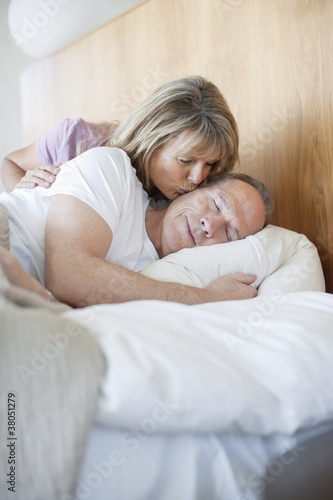Senior woman kissing man asleep in bed