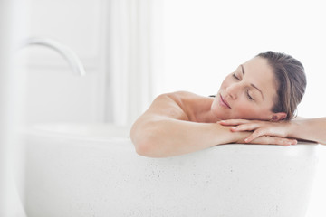 Serene woman leaning on edge of bathtub with eyes closed