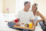 Smiling couple with breakfast on tray in bed