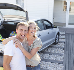 Portrait of smiling couple hugging in driveway