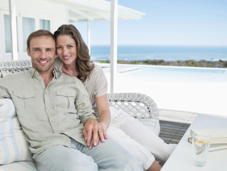 Portrait of smiling couple sitting on patio overlooking ocean