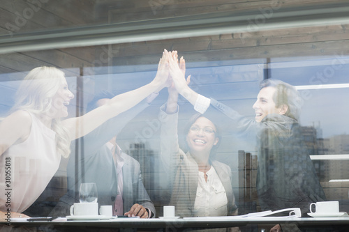 Business people joining hands in conference room