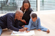 Young black family sitting on the floor drawing a picture with t