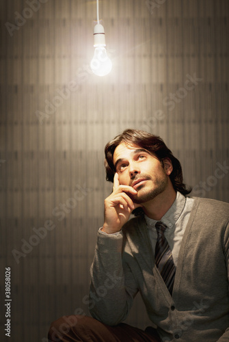 Pensive businessman sitting under illuminated light bulb