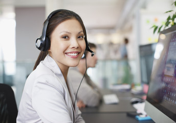 Portrait of smiling businesswoman with headset at computer in office