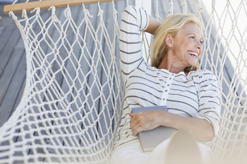 Smiling woman laying in hammock with book