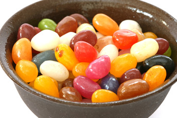 Colourful candies in a brown bowl on white background