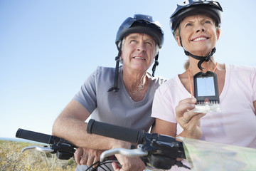 Senior couple on bicycles with compass and map