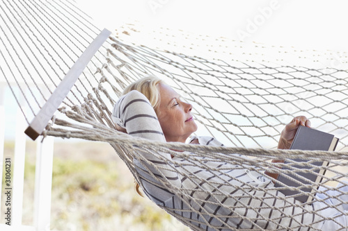 Serene woman with eyes closed laying in hammock with book