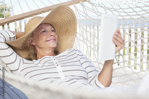 Smiling senior woman using digital tablet in hammock