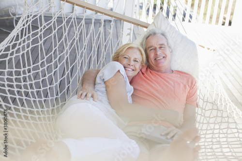 Portrait of smiling senior couple laying in hammock