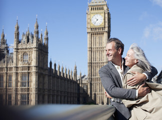 Happy couple hugging in front of Big Ben clocktower in London