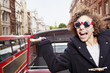 Portrait of exuberant woman wearing British flag sunglasses and riding double decker bus in London