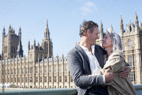 Happy couple hugging in front of Parliament Buildings in London