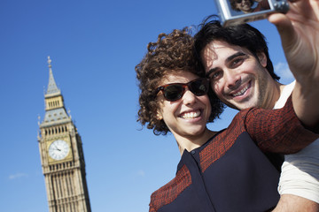 Couple taking self-portrait with digital camera below Big Ben clocktower in London
