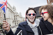 Portrait of exuberant couple with British flag and sunglasses riding double decker bus