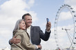 Smiling couple taking self-portrait with camera phone next to ferris wheel