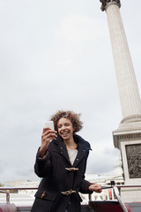 Woman holding cell phone on double decker bus below monument