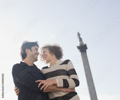 Couple smiling and hugging face to face below monument