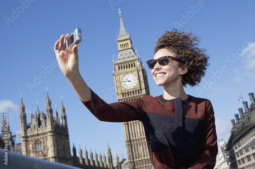 Smiling woman taking self-portrait with digital camera below Big Ben clocktower