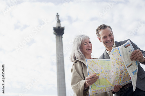 Smiling couple looking at map under monument