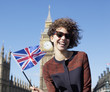 Portrait of smiling woman with British flag in front of Big Ben clocktower