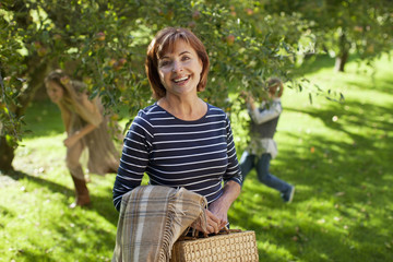 Portrait of smiling woman with blanket and bag in apple orchard