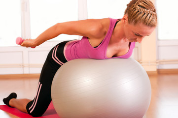 Young woman in sportswear, doing fitness exercise with fit ball