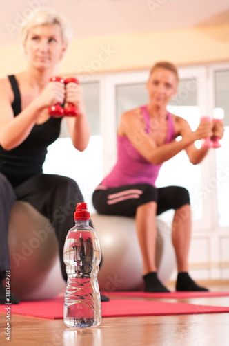 Bottle of water in front of group of people doing fitness exerci