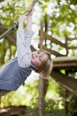 Portrait of boy hanging from rope swing