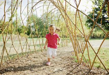 Smiling girl running under bare arbor in park