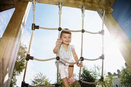 Portrait of smiling girl climbing rope at sunny playground