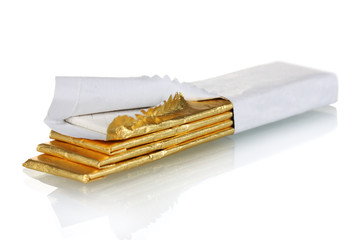 chewing gums wrapped in golden foil, isolated on white
