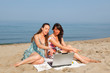 Two Women with Computer at Seaside