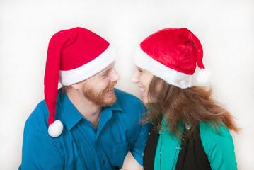 муж с женой в новогодний шапочках