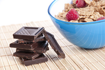 Bowl of cornflakes with raspberries and chocolate bars