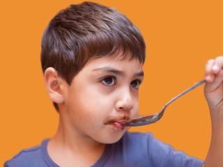 bambino che mangia crema al cioccolato con il cucchiaio