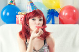 Young caucasian woman fooling about with a party horn blower poster