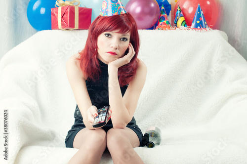 Sad red-haired party woman sitting at home and watching TV